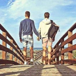 2 young guys holding hands